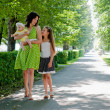 Stock Photo: Womand two children walking down avenue in park