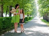 Woman and two children walking down the avenue in the park — Stock Photo