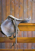 Saddle on a wooden railing — 图库照片