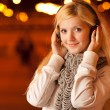 Girl in ear-phones in evening - Stock Photo