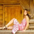 Stock Photo: Girl sits on log hut handrail