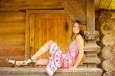 Ragazza si siede sul corrimano capanna log — Foto Stock