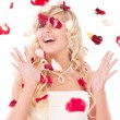 Beautiful laughing bride. On her petals of roses - Stock Photo