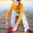Girl fastens laces on gym shoes - Stok fotoğraf