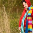 Girl in hood with multi-colored scarfs — Stockfoto