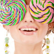 Lovely girl closes eyes two lolipops - Stock Photo