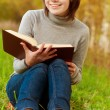 Young beautiful girl sits on bridge and reads book — Stock Photo
