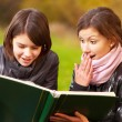 Two young attractive women reading a book — Stock Photo