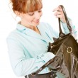Smiling young woman searches for something in handbag - Stock Photo