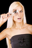 Surprised girl looks in a magnifier — Stock Photo