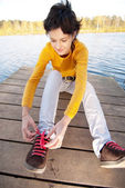 Girl fastens laces on gym shoes — Stock Photo