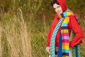 Girl in hood with multi-colored scarfs — Стоковое фото