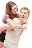Laughing girl astride young man — Stock Photo