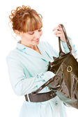 Smiling young woman searches for something in handbag — Stock Photo