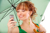 Beautiful girl with green parasol reads sms on phone — Stock Photo