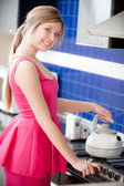 Girl in red dress holds teapot — Stock Photo