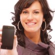 Charming girl stretches phone — Stock Photo
