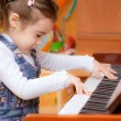 Stock Photo: Little girl plays piano