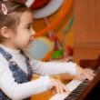 Little girl plays piano - Stock Photo