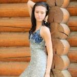 Beautiful brunette at log hut — Stock Photo #3762835