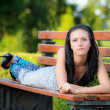 Beautiful girl lies in park — Stock Photo