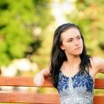 Beautiful brunette sits on bench — Stock Photo