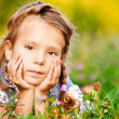 Little girl lies on lawn — Stock Photo