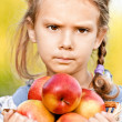 Little girl with basket of apples - Stok fotoraf