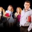 Portrait of young man-student against three girls — Stock Photo