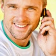 Young man speaks on phone — Stock Photo