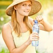 Girl in straw hat drinks water - Stock Photo