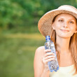 Girl in straw hat drinks water — Stock Photo