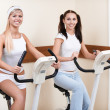 Girls on excercise bikes - Stock Photo