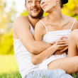 Young beautiful couple sits on grass — Stock Photo
