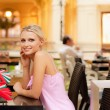 Smiling girl sits at little table at restaurant — Stock Photo #3764837