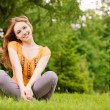 Beautiful girl sits on lawn — Stock Photo #3764906