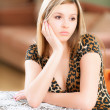 Sad girl sits at table — Stock Photo #3764973