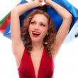 Stock Photo: Rejoicing girl in red dress with purchases