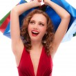 Rejoicing girl in red dress with purchases - Stock Photo