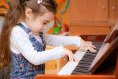 Little girl plays piano — Stock Photo