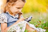 Little girl draws on PDA — Stock Photo