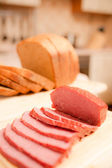 Сut bread and sausage on table — Stock Photo