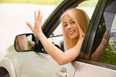 Driver-woman of car waves back — Stock Photo