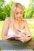 Dívka student zapisuje do psaní knihy — Stock fotografie