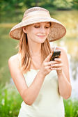 Girl in straw hat with phone — Stock Photo