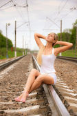 Girl sits on metal rails — Stock Photo
