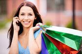молодой улыбается женщина для покупок и телефонные. — Стоковое фото