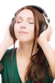 Lovely smiling girl in ear-phones blindly — Stock Photo