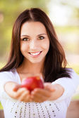 Mujer joven extiende apple — Foto de Stock