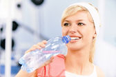 Sportswoman drinks water — Stock Photo